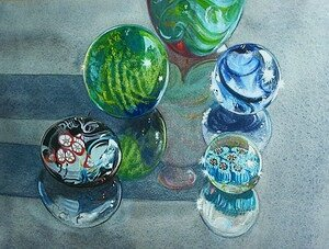 Glass jar and Paperweights on glass table top.