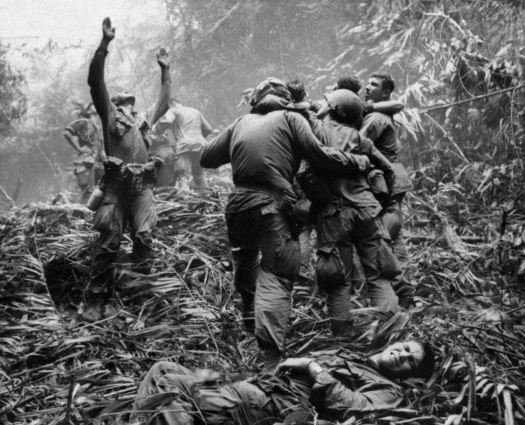 In a 1968 Associated Press photo from Vietnam by Art Greenspon, a soldier guides an unseen medevac helicopter to a jungle clearing where wounded comrades wait.