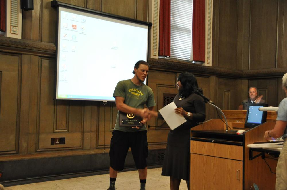 Derek Daniels accepting the Golden Wheel Award from Mayor Bellamy.