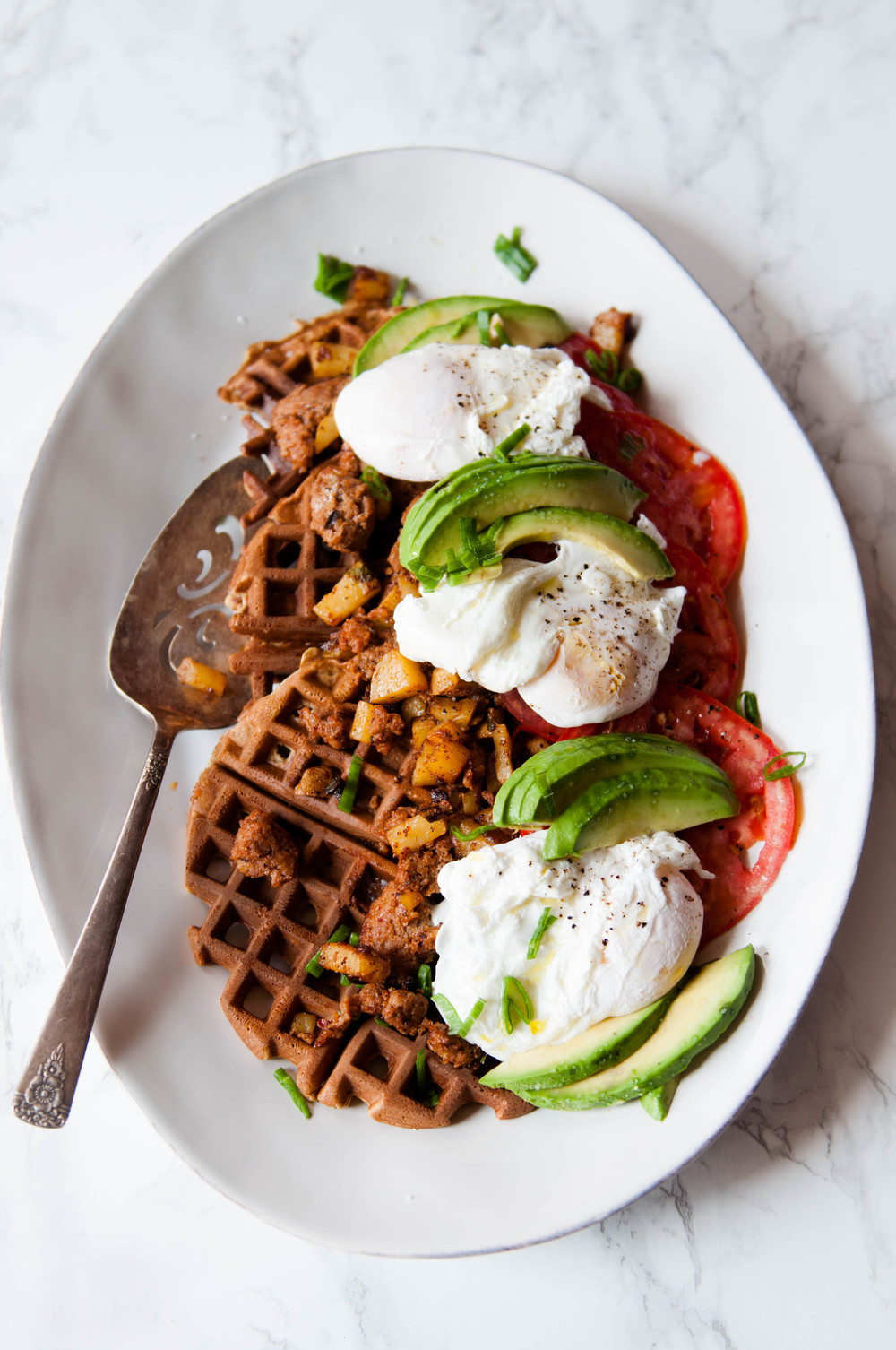 Chickpea and Einkorn Waffles with chorizo hash, poached eggs, sliced Summer tomatoes and avocado