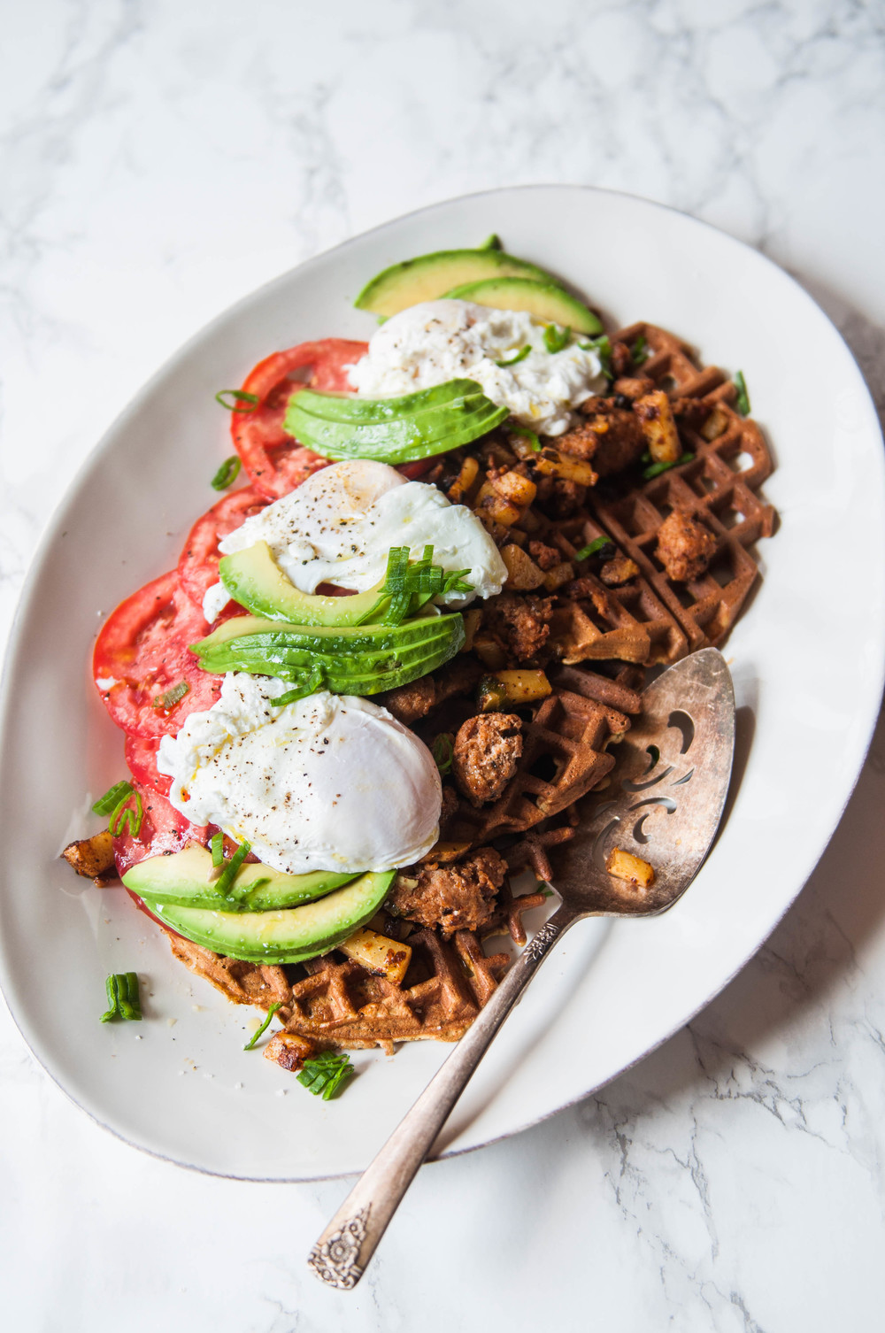Chickpea and Einkorn Waffles with chorizo hash, poached eggs, sliced Summer tomatoes and avocado.