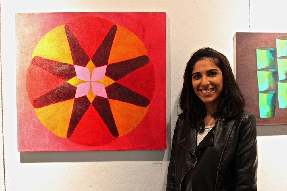 Misha Sumar '16 stands next to her work