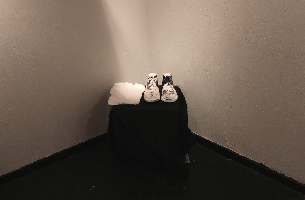 Cement filled shoes created by Tuyen Nguyen '17 quietly occupied a corner of the room. Photo by Lexie Brown '17