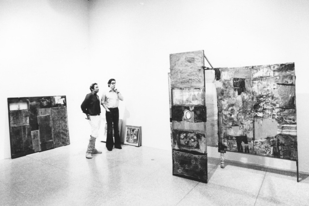 Rauschenberg and Walter Hopps discussing *Minutiae*(1954) during the installation of the retrospective exhibition *Robert Rauschenberg*, National Collection of Fine Arts, Smithsonian Institution, Washington, DC, 1976.  Photo: Gianfranco Gorgoni via Artsy.net