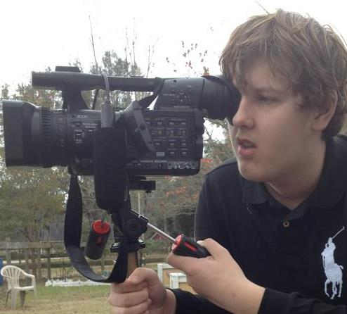 Blease posing with his camera as he shoots one of his films.
