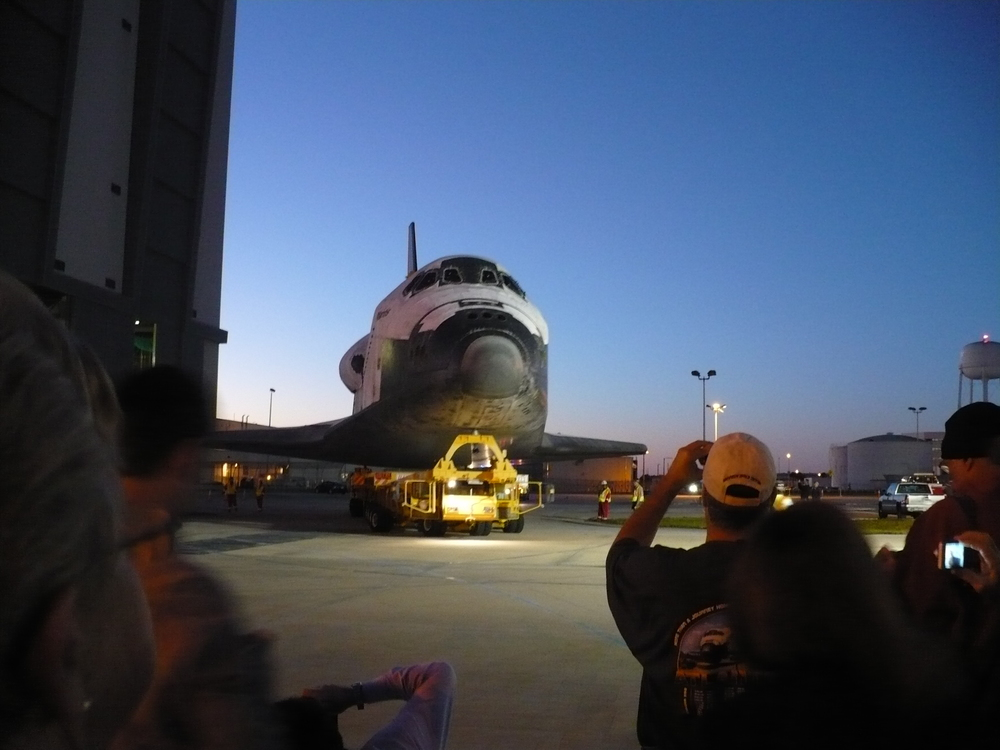 Space Shuttle Atlantis sits in front of the VAB and a rising sun as she prepares for her journey to the KSCVC, her new home. Credit: Mary Ratterman
