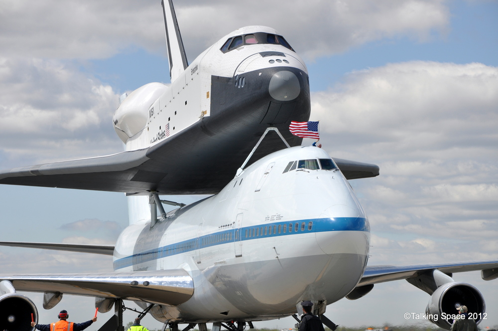 Space Shuttle Enterprise taxiing to its parking spot in front of the grand stands set up at the airport as a pilot holds the American flag out the window. Credit: Sawyer Rosenstein