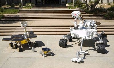A size comparison of the Mars Exploration Rovers (MERs) on back-left, Sojourner, a small rover onboard Mars Pathfinder on front-left, and the Curiosity Rover on right. Credit NASA/Jet Propulsion Laboratory