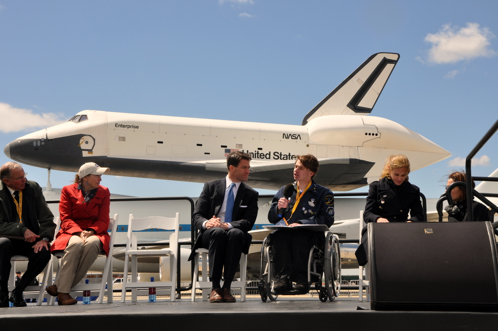 Sawyer Rosenstein gives his speech at the welcoming ceremony for the Space Shuttle Enterprise, sitting behind him on the runway at JFK Airport in New York City. Credit: Joel Rosenstein