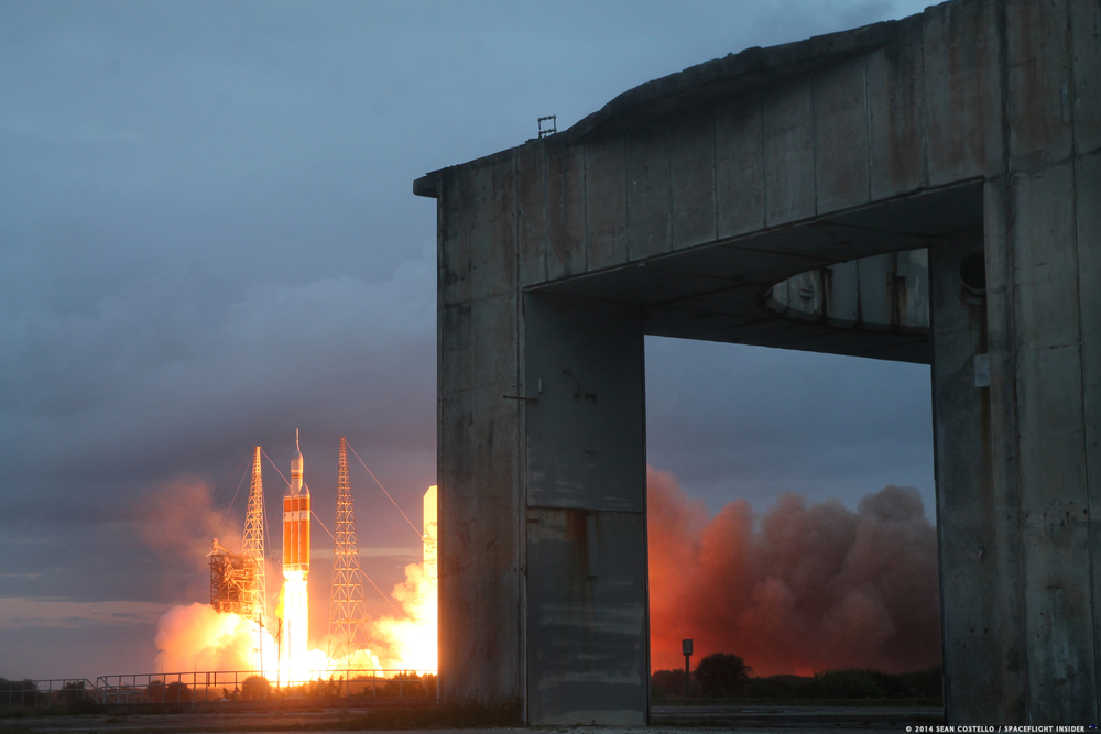 The past and future come together in one image as the Delta IV Heavy carrying Orion lifts off in the background with Launch Complex 34, launch pad of Apollo 1, in the foreground. Credit: Sean Costello/SpaceFlight Insider