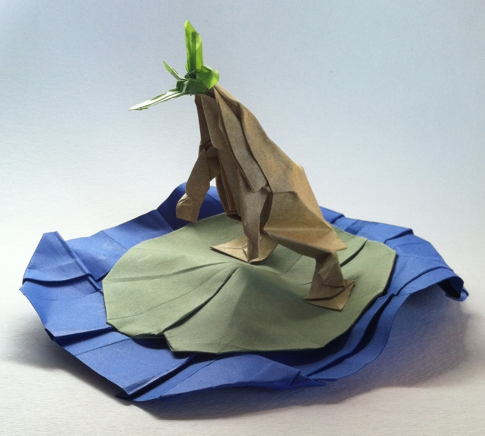 My latest origami design is inspired by my childhood love of frogs. In this piece I tried to capture the grace of a jumping frog as it lunges for its prey.     Folded from four pieces of uncut paper, dragonfly: vellum, frog: elephant hide, lilypad: canson, and water: card stock. Designed and folded by Blake Derksen.