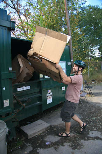 Dumping cardboard into the recycling dumpster.