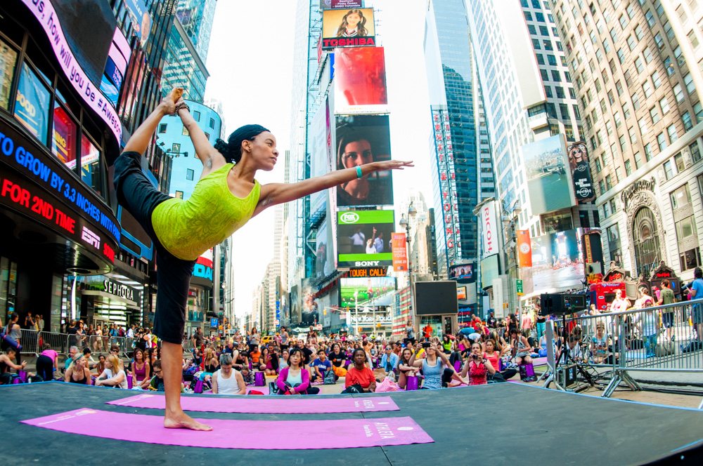A beautiful yogini practices Natarajasana (dancer's pose) with the backdrop of Times Square