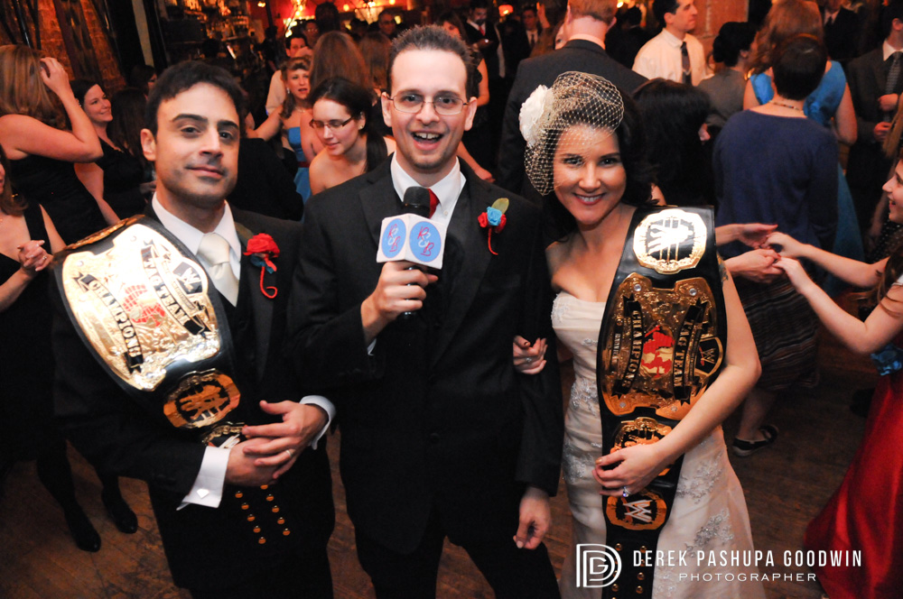 The bride and groom with their wrestling championship belts