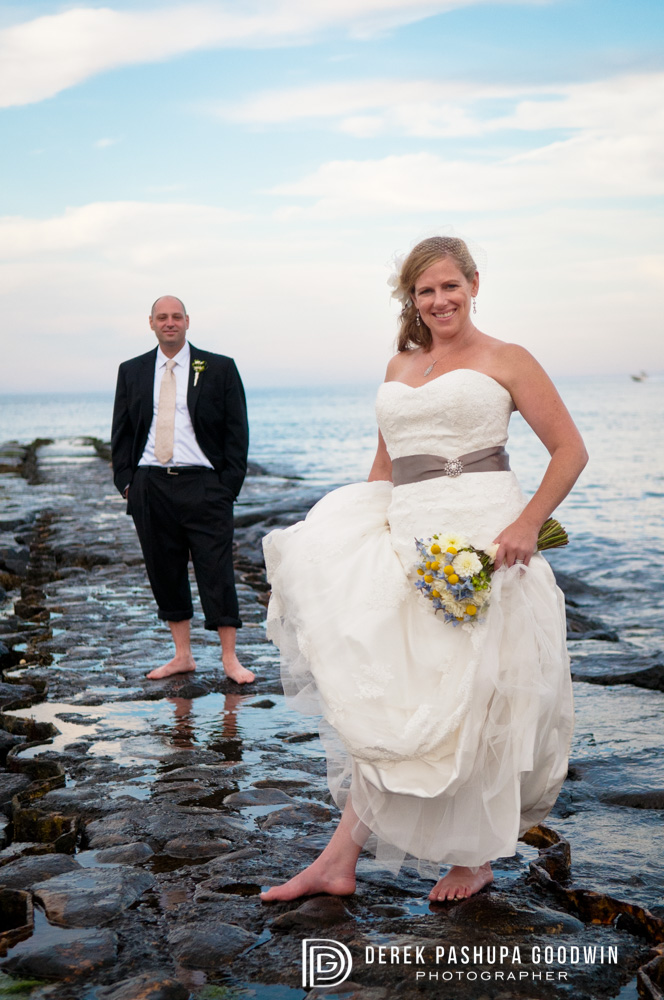 the bride and groom on a Block Island pier with the ocean behind them