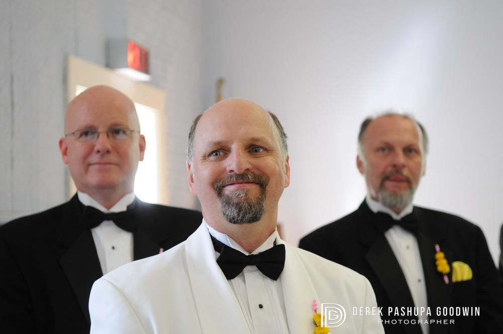 Groom and groomsmen look on as bride enters church