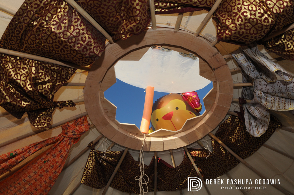 A floating monkey balloon peeks in through the hole at the top of our yurt at Spiral Monkey Camp