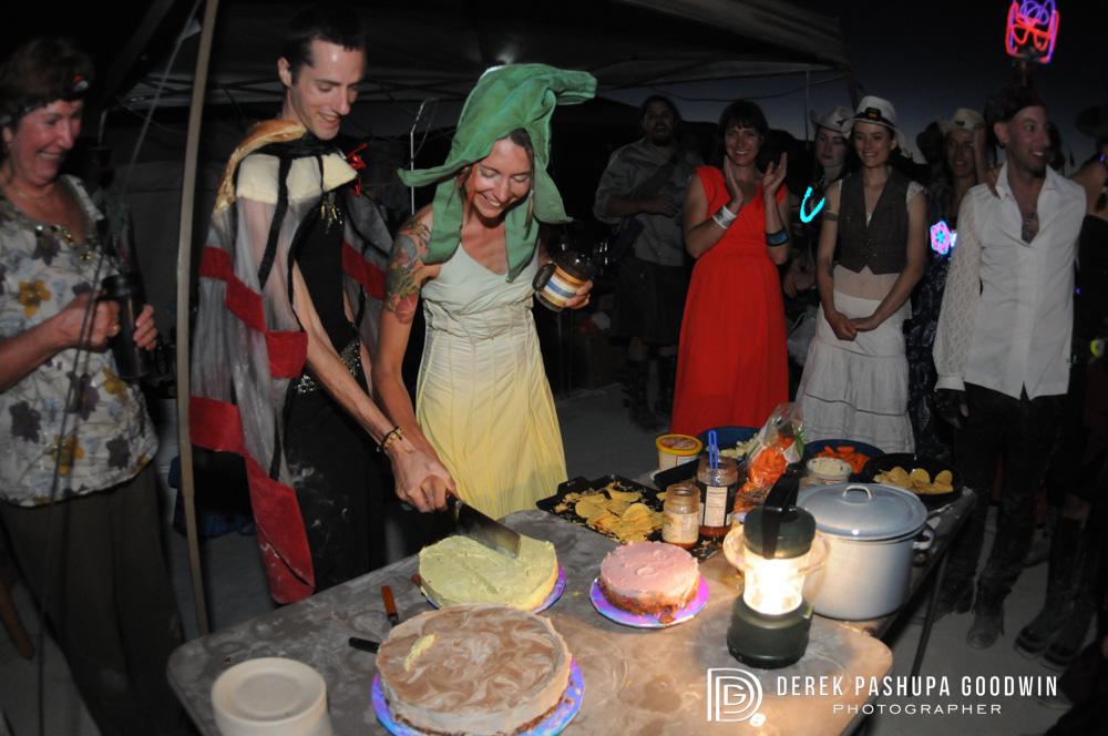 bride and groom cut the raw vegan cake at burning man
