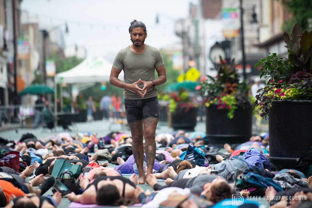 Teacher Jai Sugrim walks amongst students resting in shavasana;Yoga Fest Jersey City