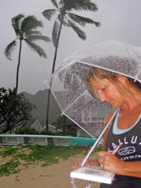 Kirsten working on a project in a passing rain squall. Lanikai, Oahu