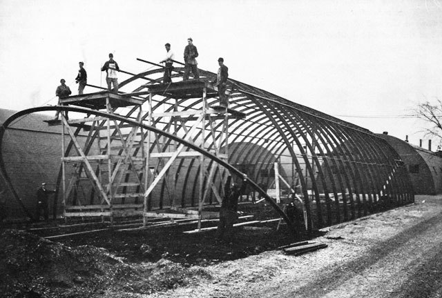 The School Hut at the Central Spare Parts Warehouse, Joliet, Il. Showing the erection of a 40-by-100 foot quonset hut in the Seabee camp area. Photo from the Naval Historical Center via ibiblio.org.