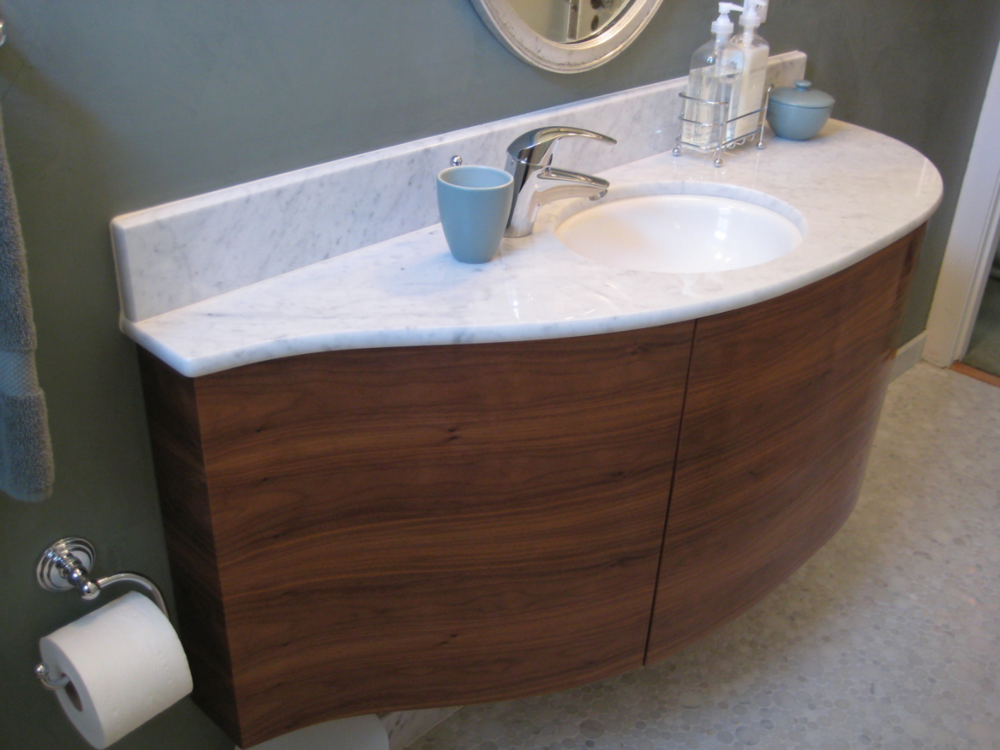 This custom floating walnut vanity is topped with marble to match the circles marble mosaic tile floor.  Walls are a sea blue Venetian plaster.