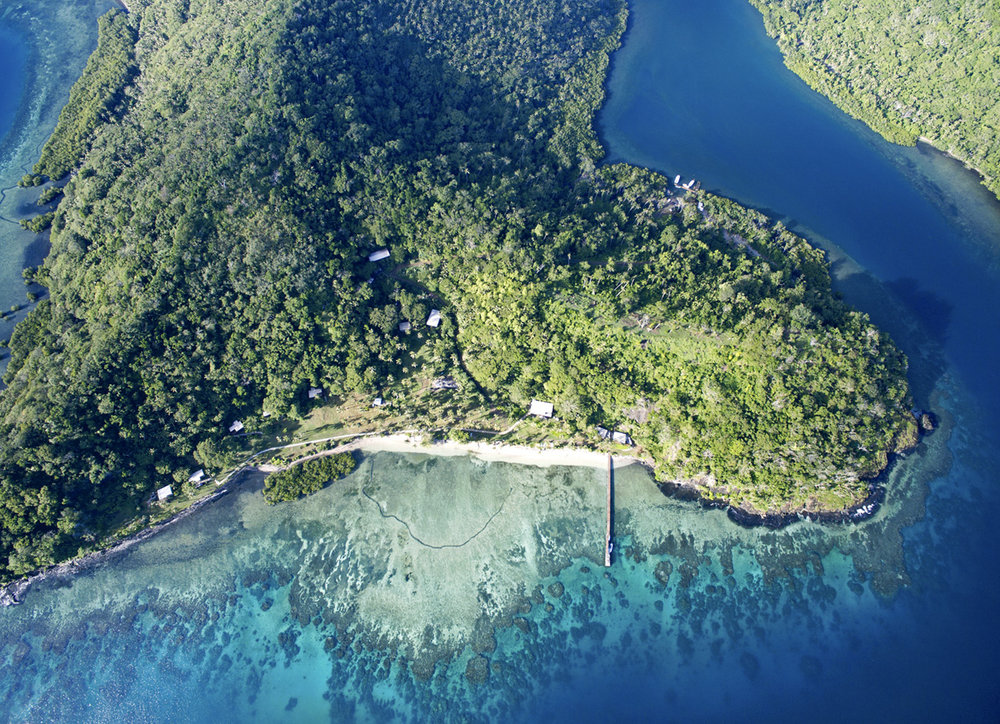 Aerial shot of The Remote Resort Fiji Islands.  From left to right the villas are: Royal Retreat, Two-bedroom Villa, Oceanfront Villas (3), Storage building, Two-bedroom Royal Retreat, Main Pavilion, Oceanfront Retreats (2) at end of the jetty.  The three buildings further up the hill are the staff house, office and managers house.