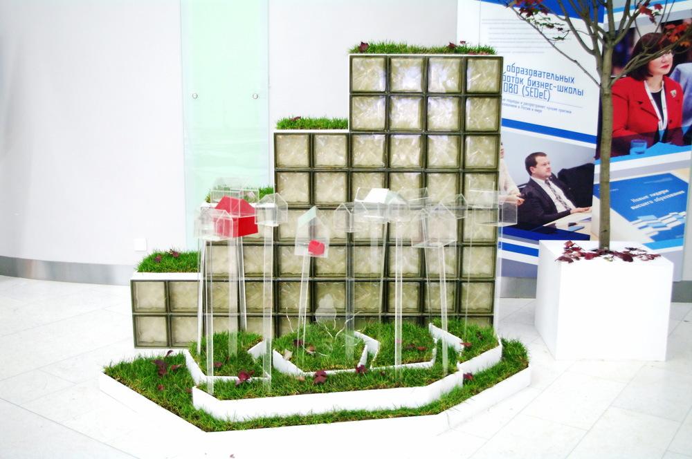 Стенд выполнен в стилистике архитектуры поселка, подиум отображает план застройки.