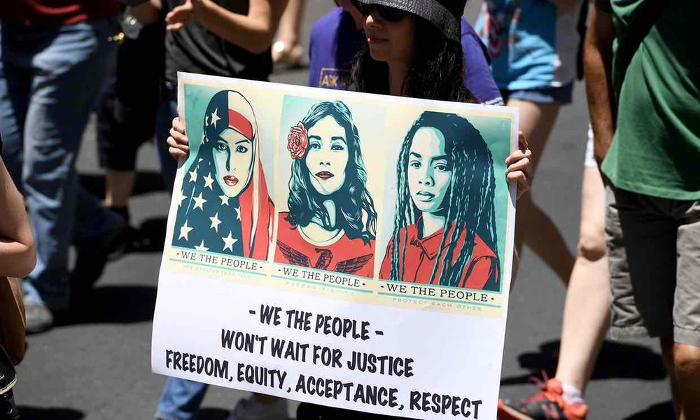 A protester in Sydney, Australia, holds a placard with images from the We The People project designed by Shepard Fairey. Photograph: Dan Himbrechts/AAP
