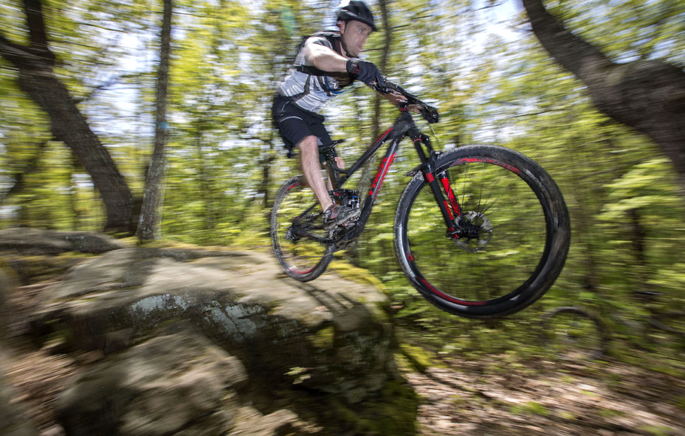 Carl Holdren drops off a rock on Pine Ridge Trail in Kanawha State Forest.