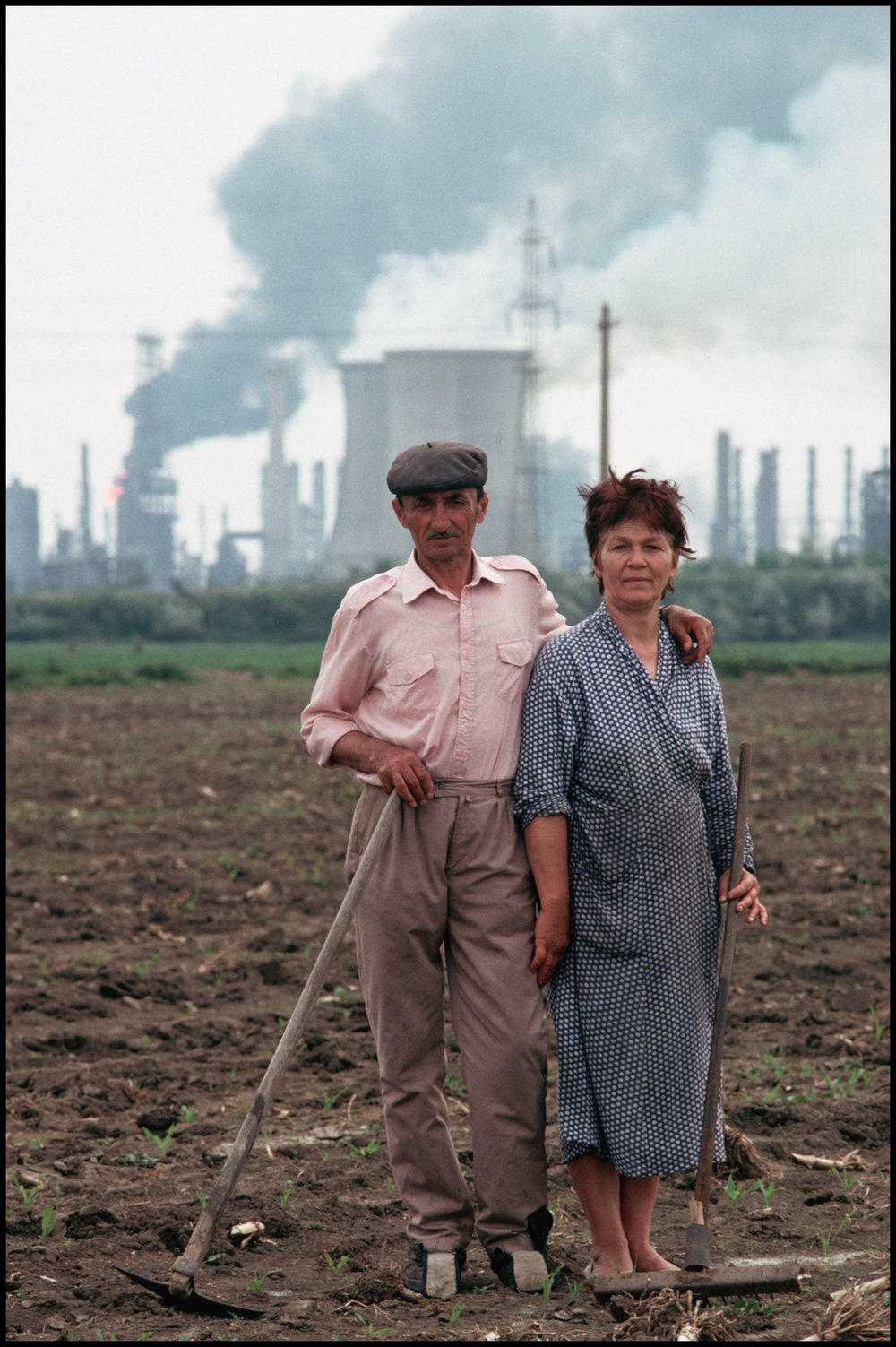 May 1990, Romania --- A portrait of a farming couple in a field outside of Bucharest. A series of factories spewing smoke can be seen in the distance