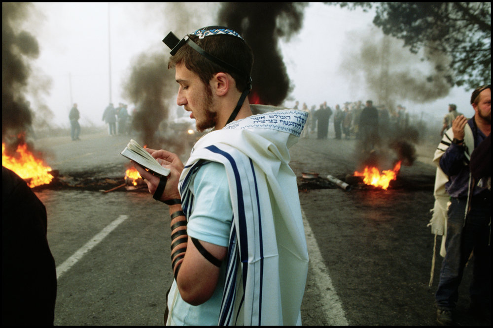 1993, West Bank --- Walking past flames in the street, an Orthodox Jewish settler wearing phylacteries prays during a morning demonstration in the West Bank