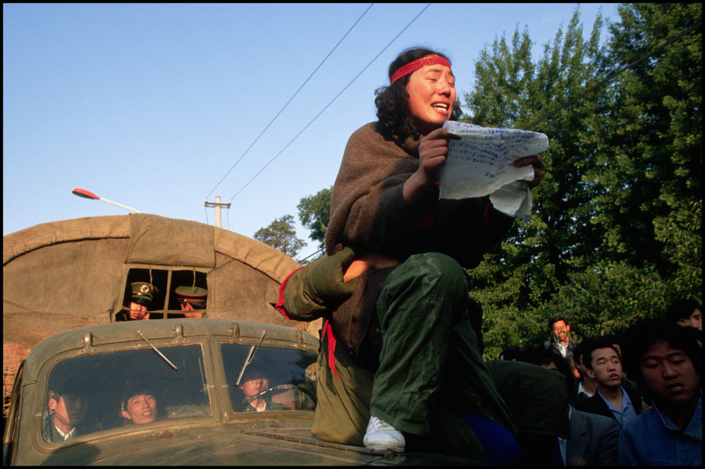 ca. 1989, Beijing, China --- A demonstrator reads aloud from the hood of a military truck during a student protest in Tiananment Square.