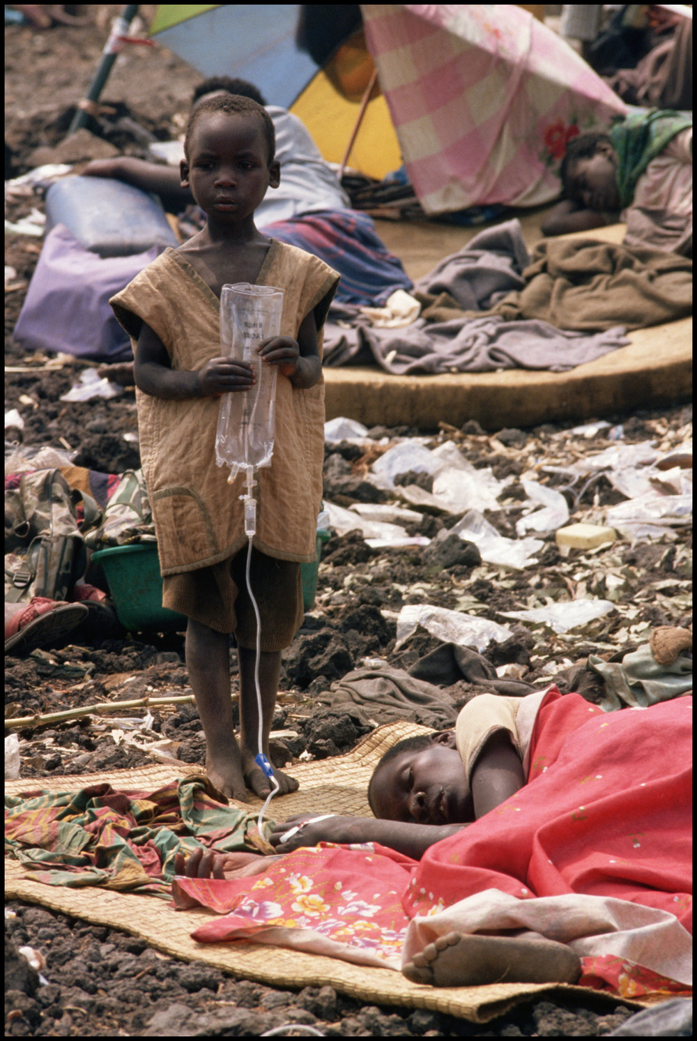1994, Goma, Democratic Republic of the Congo --- A Hutu boy holds an IV bag for a cholera-stricken adult, possibly his parent, in a Rwandan refugee camp in Goma, Zaire