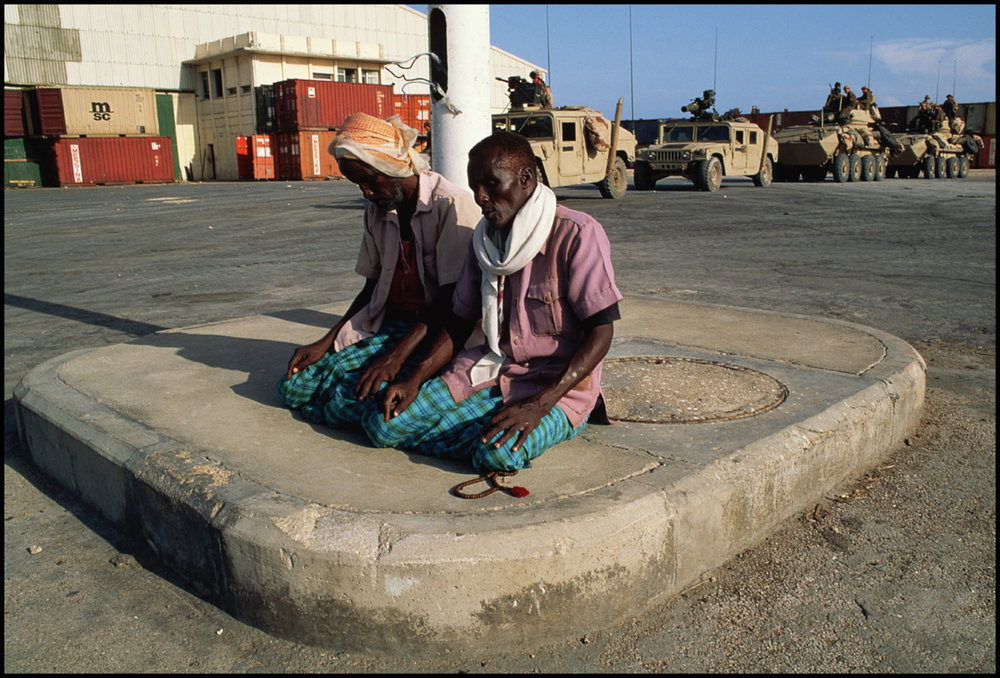 15 Dec 1992, Mogadishu, Somalia --- Two Muslim men kneel and pray at a Mogadishu airport as international troops arrive with aid