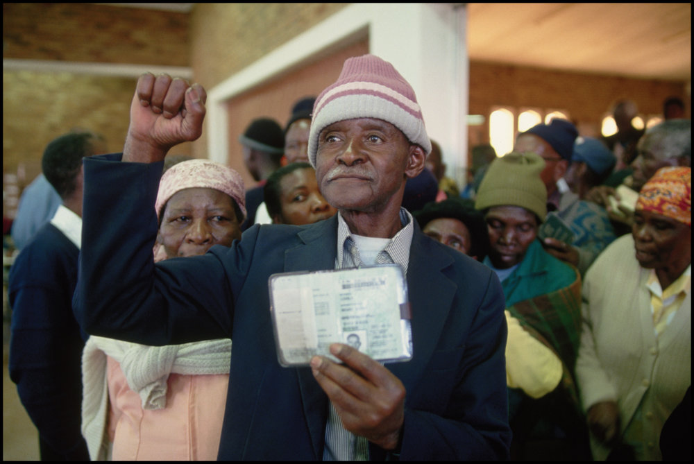 May 1994, South Africa --- A South African man displays his identification card in a polling station. He is voting on South Africa's first post-apartheid election
