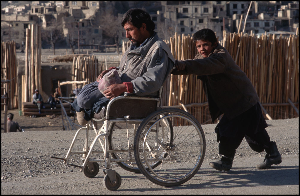 March 1996, Kabul, Afghanistan --- A double-amputee land mine victim is pushed in a wheelchair by his young son through the streets of Kabul