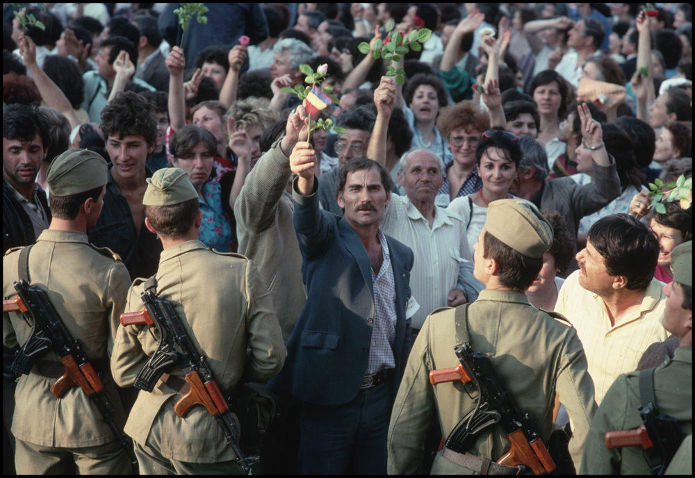 1989, Bucharest, Romania --- A man holds up a small Romanian flag attached to a rose during a rally for Ion Iliescu and the National Salvation Front during the elections of 1990.