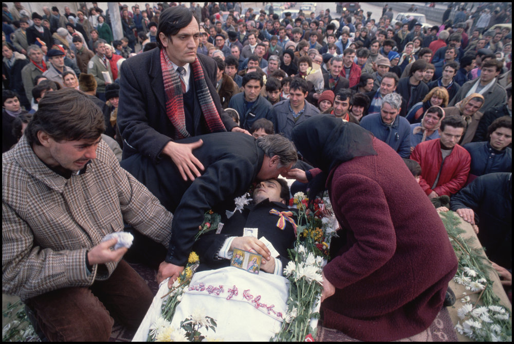 December 1989, Bucharest, Romania --- Grieving family members gather around a loved one's coffin to say goodbye during a burial ceremony at Bucharest's Belo Cemetery.