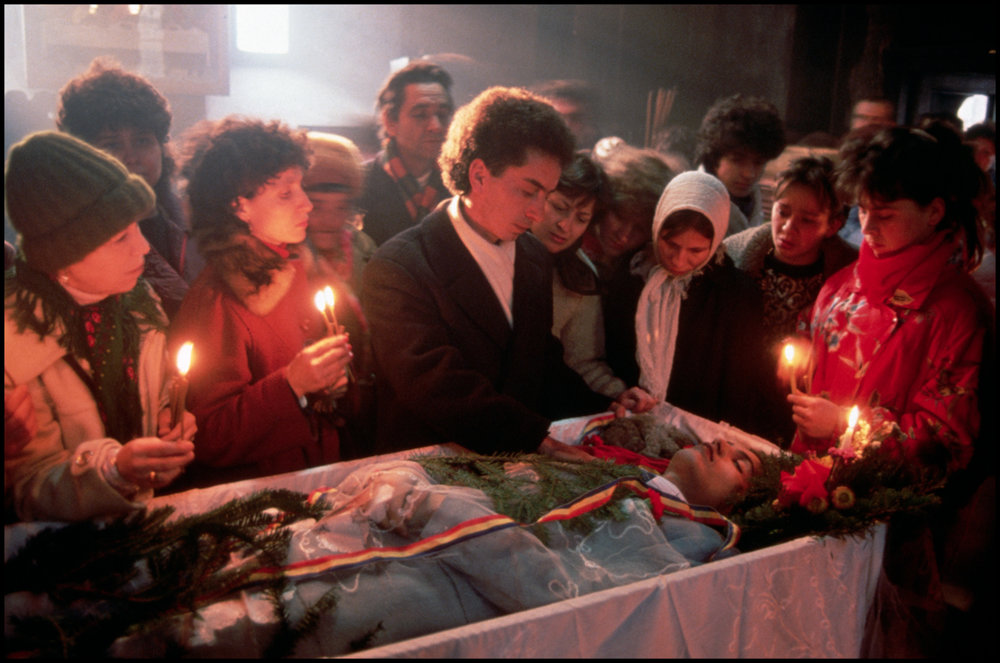 1990, Bucharest, Romania --- At a church funeral, grieving family members gather around a loved one's coffin to say goodbye. The dead man was killed in fighting during the December 1989 revolution.