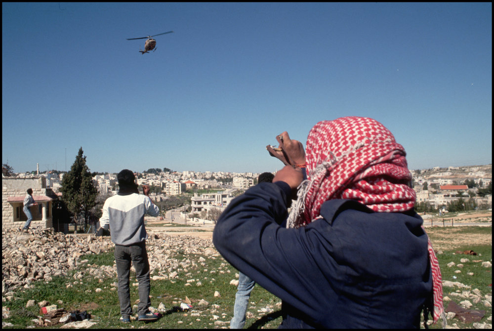 16 Mar 1988, West Bank --- Palestinians throw rocks at a helicopter of the occupying Israeli military forces.
