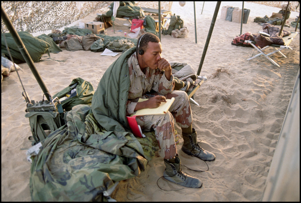 ca. December 1990, Saudi Arabia --- An American soldier takes a few moments to write home while stationed in Saudi Arabia.