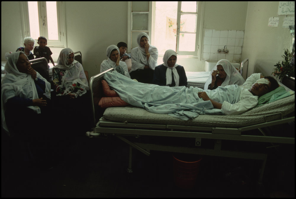 July 1988, Gaza, Gaza Strip --- A Palestinian who was shot in the face with a rubber bullet by an Israeli lies in Shifa Hospital with concerned visitors by his bedside.