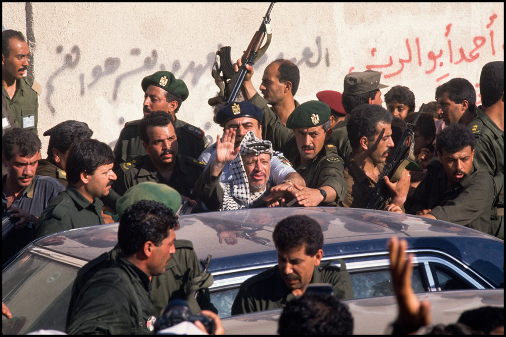 1994, Gaza, Gaza Strip --- Yasser Arafat, leader of the Palestine Liberation Organization, waves to a crowd at the Jabaliya camp where the Intifada began.