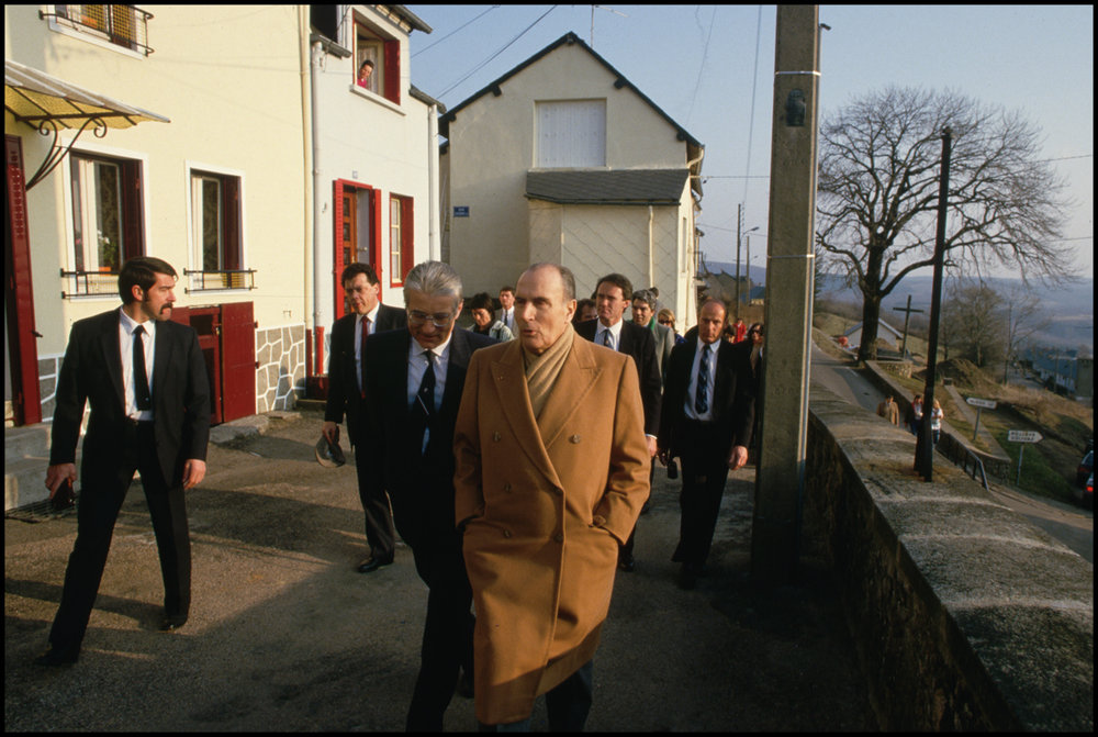 1986, Chinon, France --- French president Francois Mitterrand strolls by houses in Chinon with bodyguards and various dignitaries on a cold day.