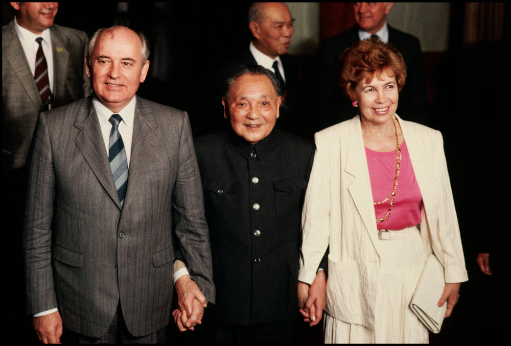 1989, China --- China's head of state, Deng Xiaoping (center), holds the hands of Mikhail and Raisa Gorbachev during a visit by the Soviet leader to China.