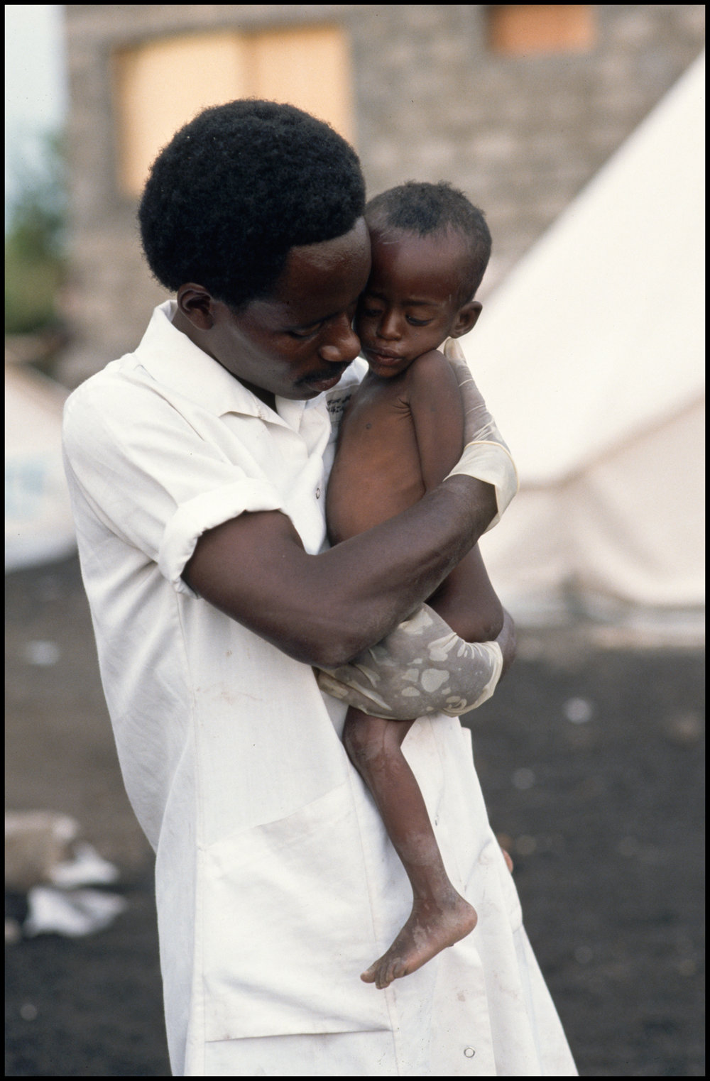1994, Goma, Democratic Republic of the Congo --- An aid worker in a refugee camp lovingly holds a young Rwandan Hutu refugee.