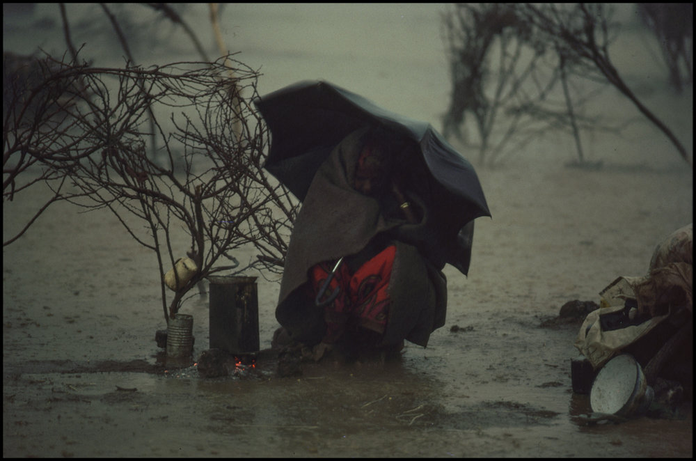 1986, Somalia --- An Ethiopian refugee with no shelter waits out a rainstorm under an umbrella.