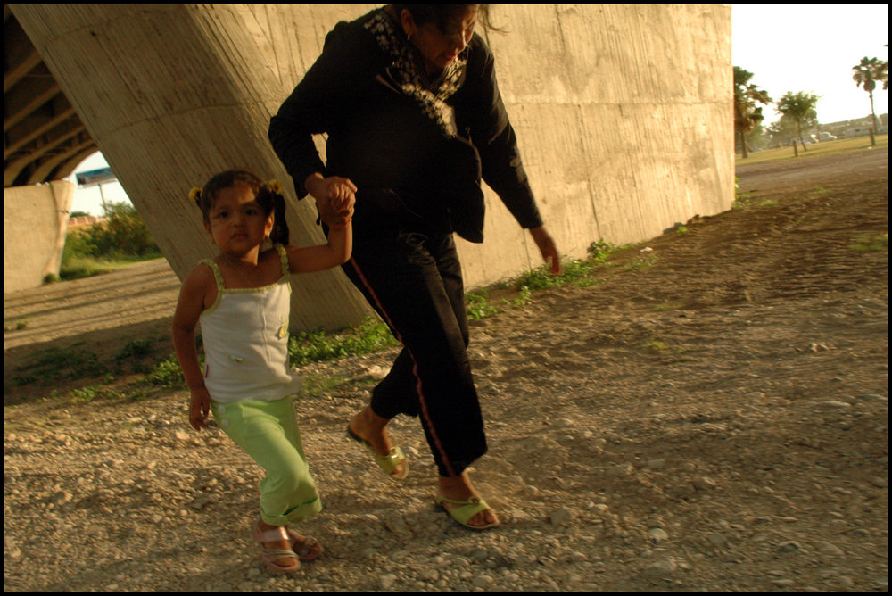 20 Jun 2006, Laredo, Texas, USA --- A woman and her daughter running under the Gateway to the Americas International Bridge, in Laredo, Texas.
