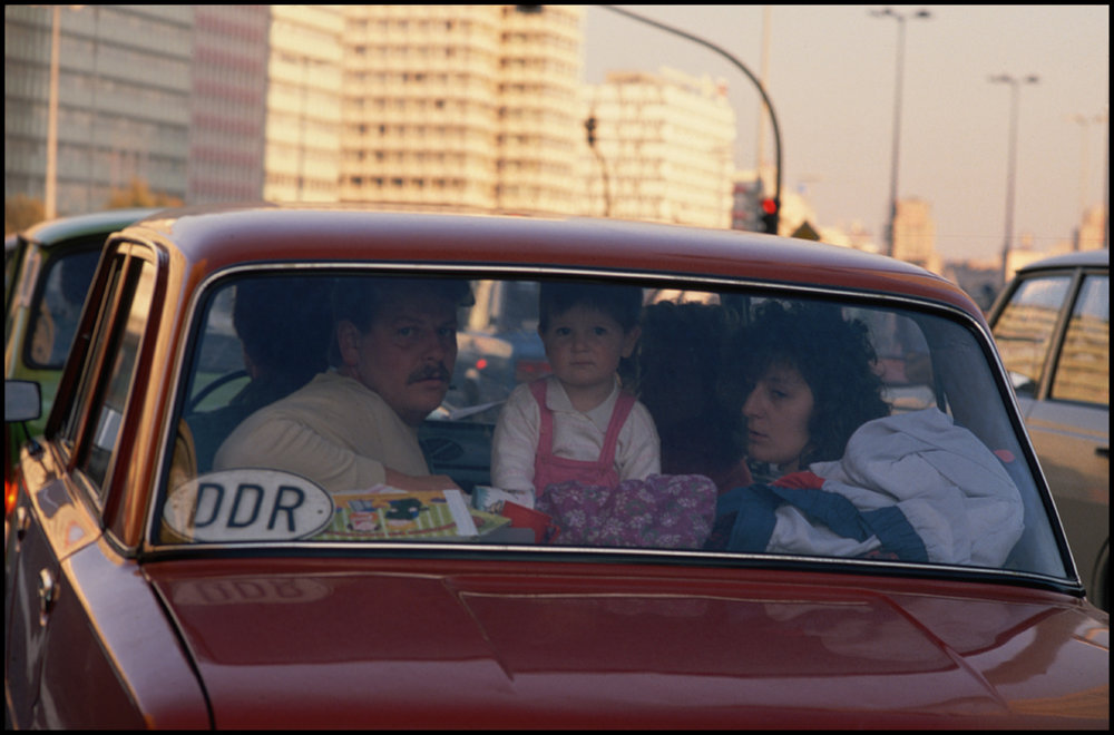 October 1989, Berlin, Germany, Germany --- An East German family looks out from the rear window of a Trabant in East Berlin